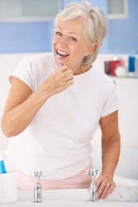Pretty Senior Woman Brushing Her Teeth Over a Sink
